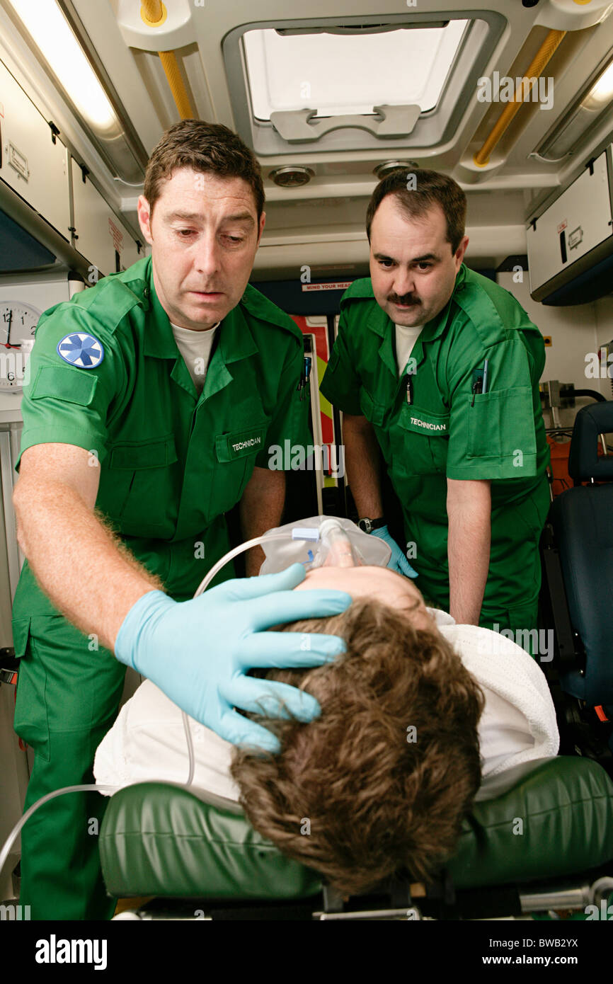 Ambulance technicians caring for patient - Stock Image