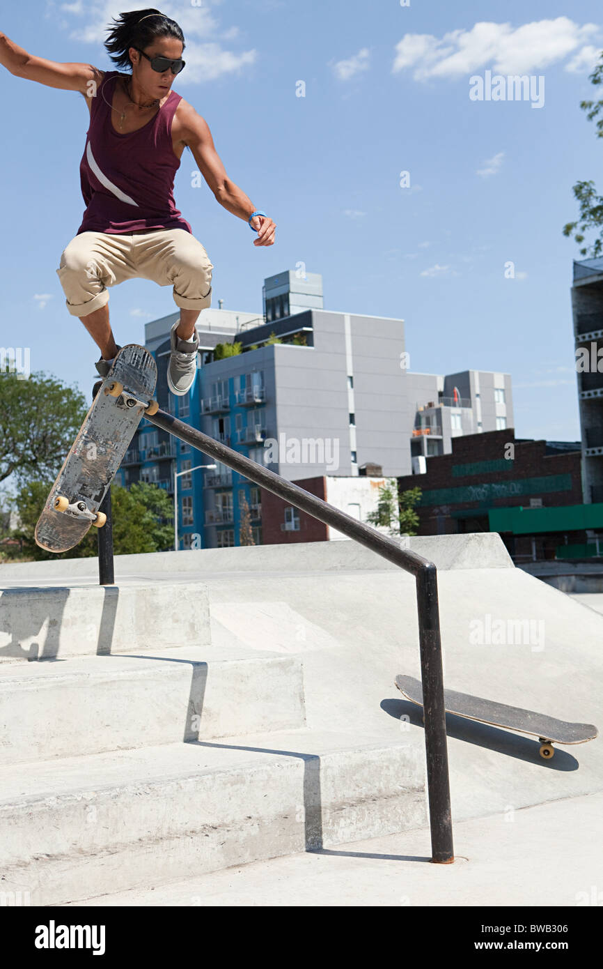 Skateboarder jumping over a rail - Stock Image