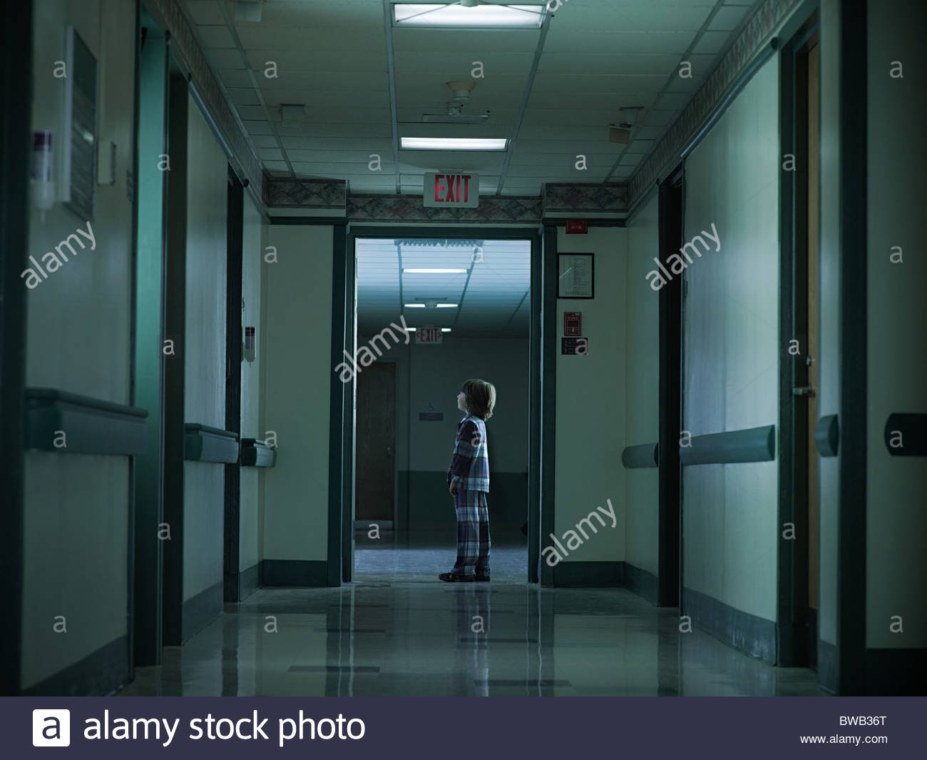 Young boy standing alone in hospital corridor - Stock Image