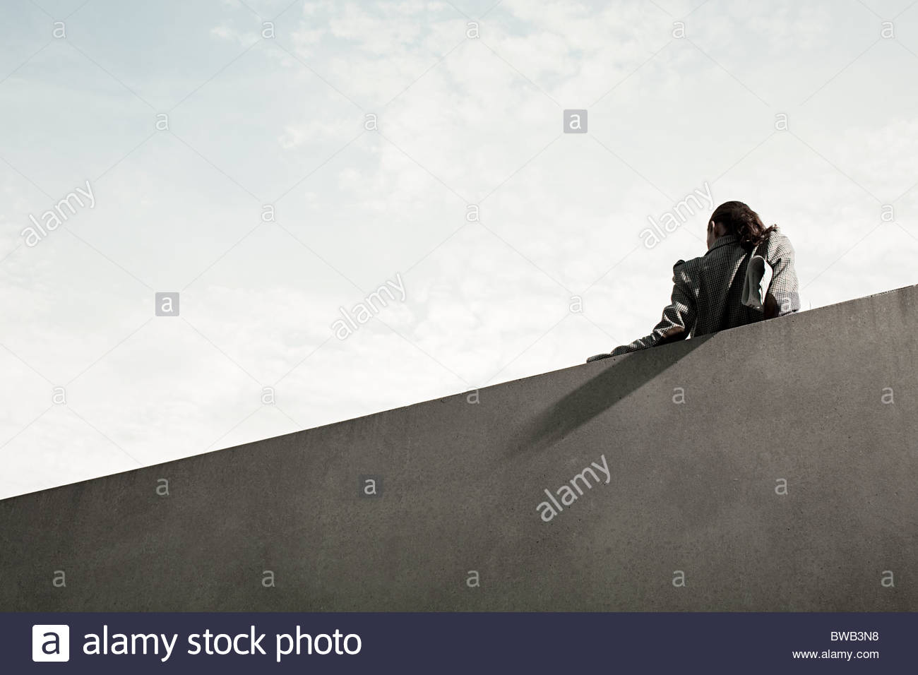 Businesswoman by wall, rear view, low angle - Stock Image