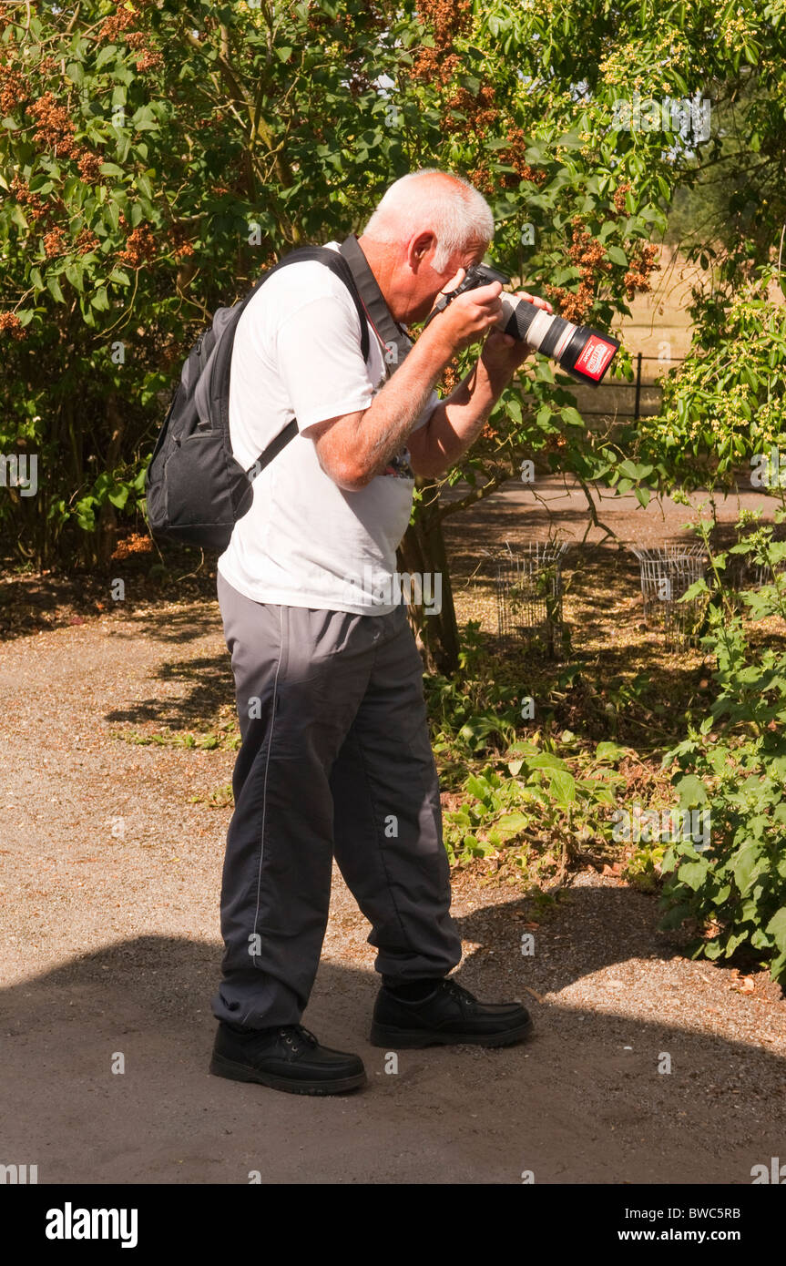 A man taking pictures with a DSLR digital camera in the Uk - Stock Image