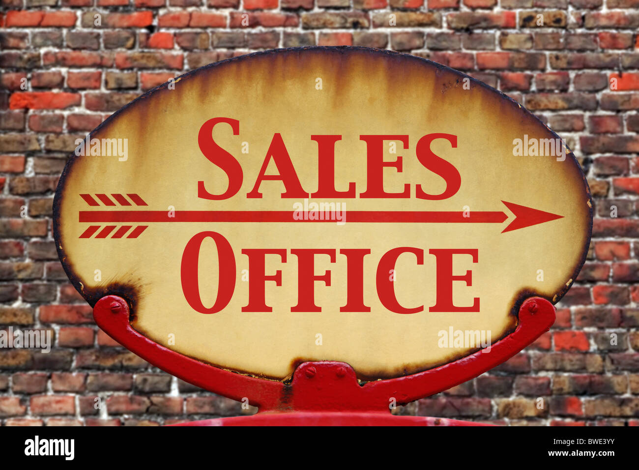 A rusty old retro arrow sign with the text Sales Office - Stock Image