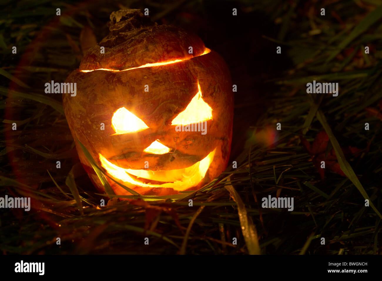 illuminated halloween turnip jack-o-lantern to ward off evil spirits. Traditionally in Ireland turnips or swedes - Stock Image