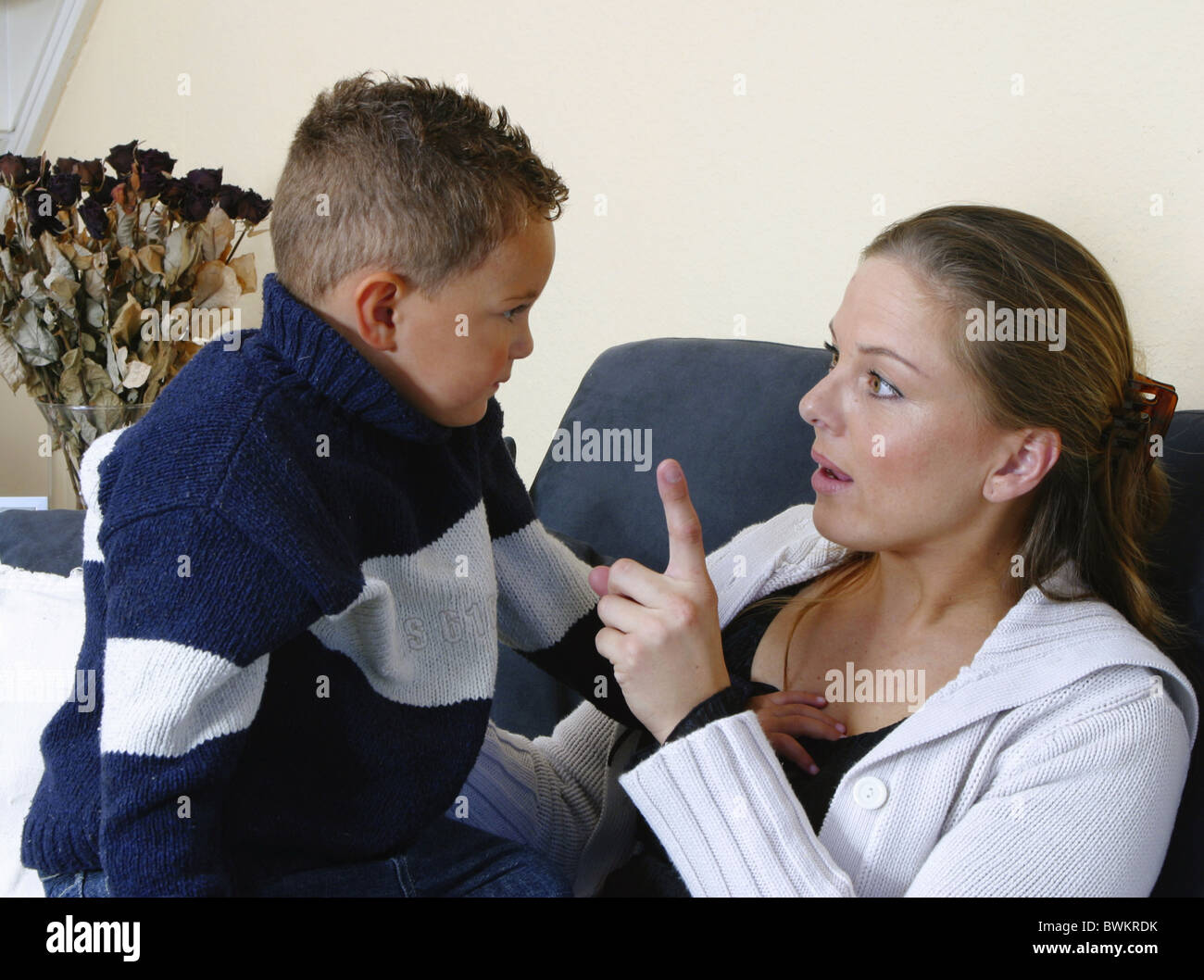 Strict and indulgent mother discipline little naughty boy told off at home Stock Photo