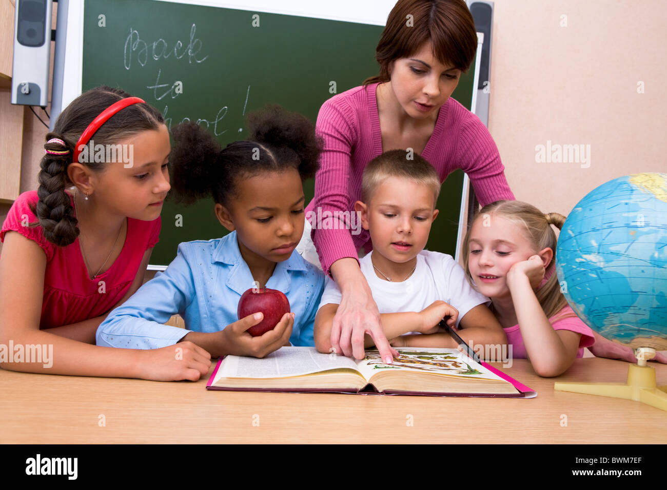 Portrait of woman teaching children and pointing to the book - Stock Image