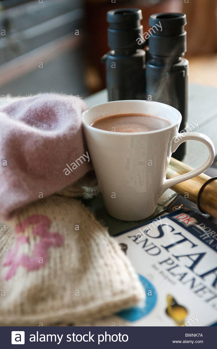 Woollen hat & scarf, mug of hot chocolate, telescope & binoculars & book on the stars & planets. - Stock Image