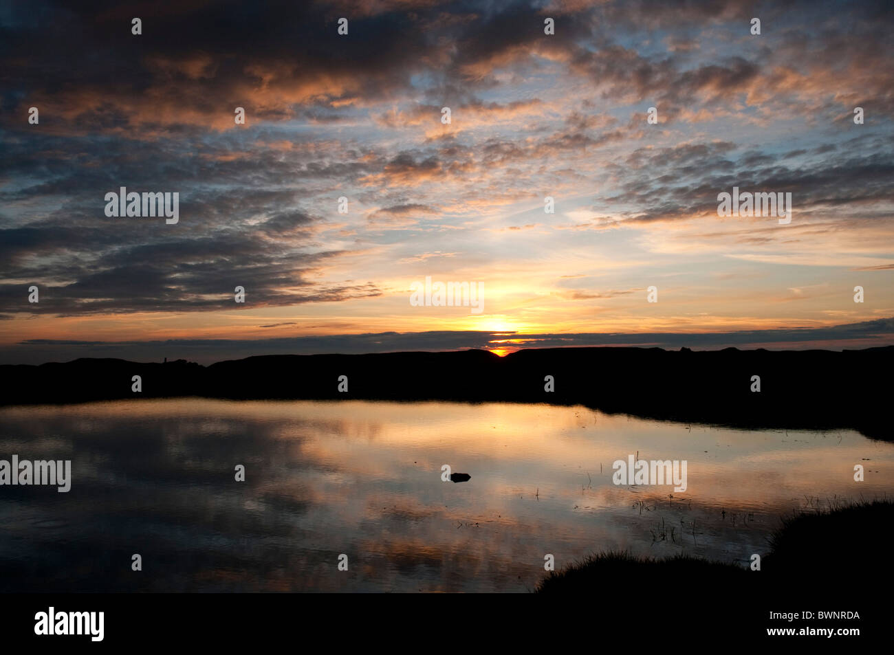 Reflections of sunset and clouds in water of pond on Dartmoor, Devon UK - Stock Image