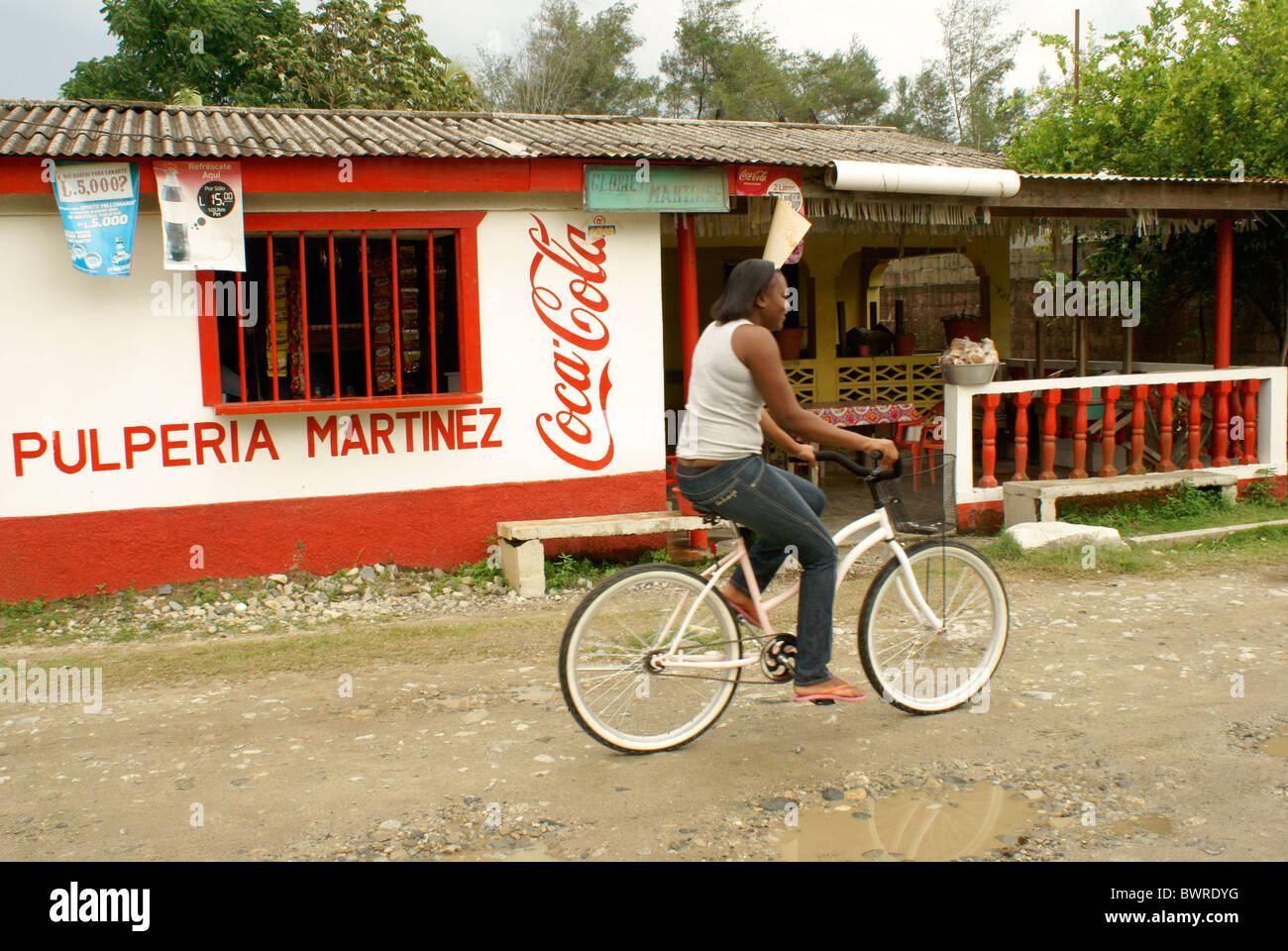 garifuna-woman-riding-a-bicycle-in-the-garifuna-village-of-triunfo-BWRDYG.jpg