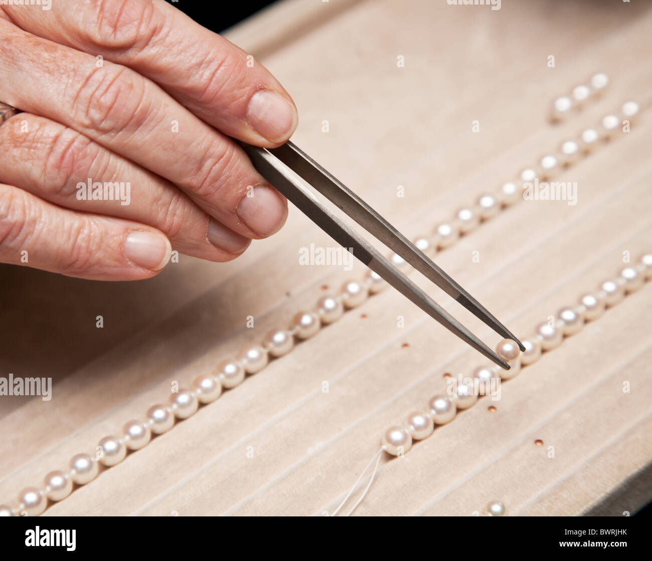 Close hand jeweler stringing pearls on a necklace - Stock Image