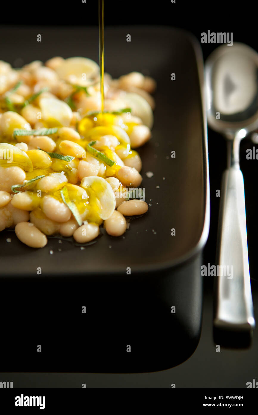 Boiled white beans served with garlic, sage and Extra virgin olive oil - Stock Image