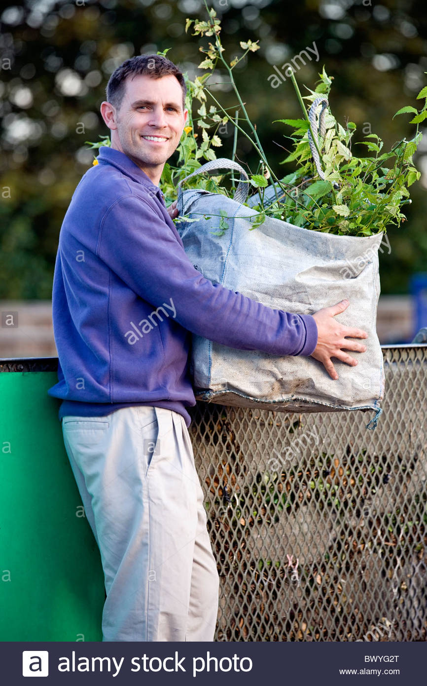 A mid-adult man recycling garden waste - Stock Image