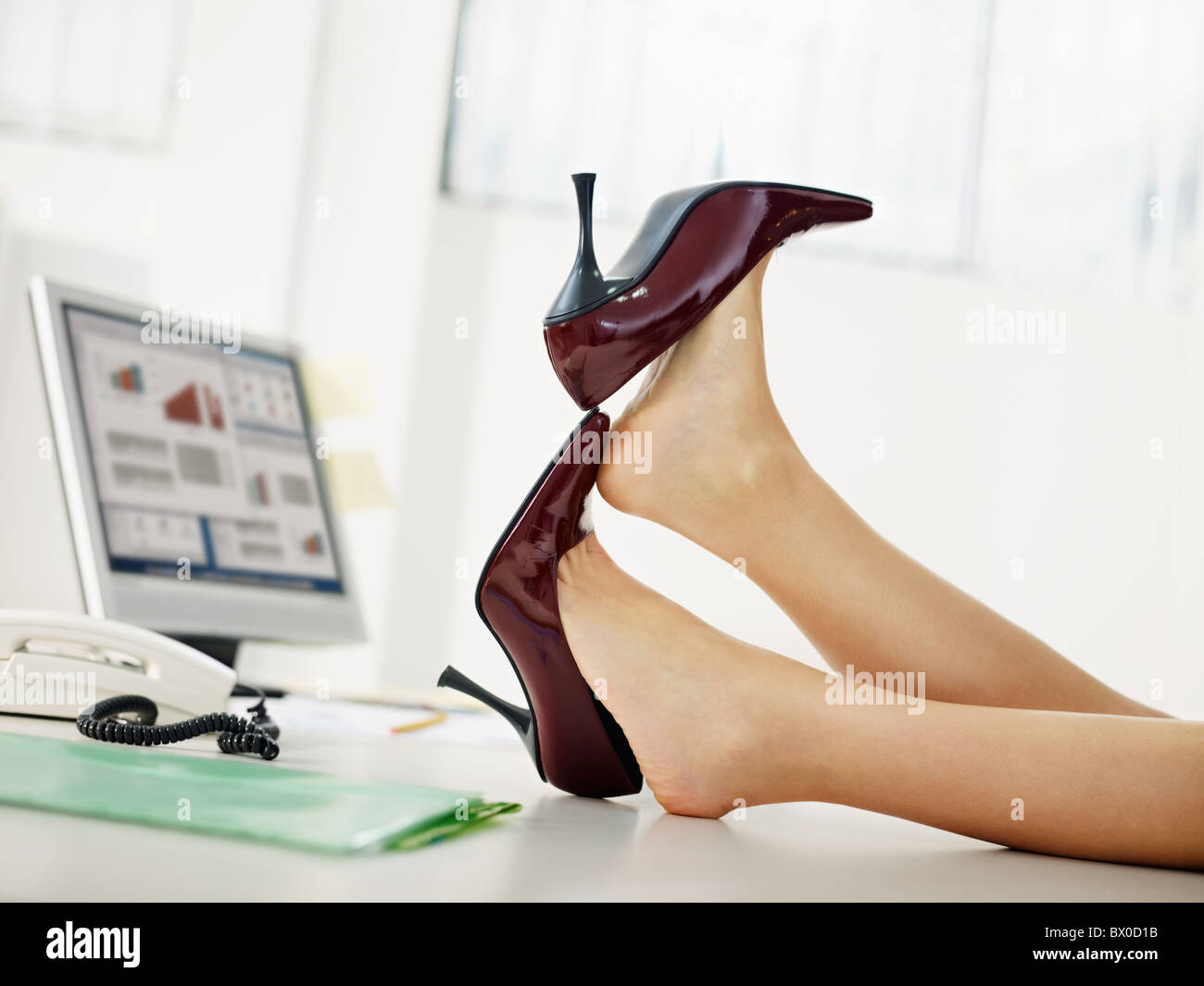woman taking off shoes in office - Stock Image