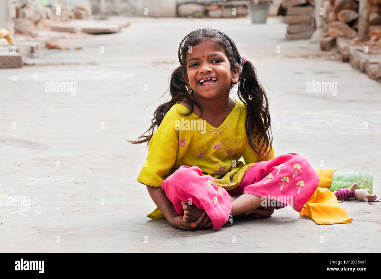 Smiling happy Indian village girl with a soft toy sitting in the street. Kothacheruvu, Andhra Pradesh, India - Stock Image