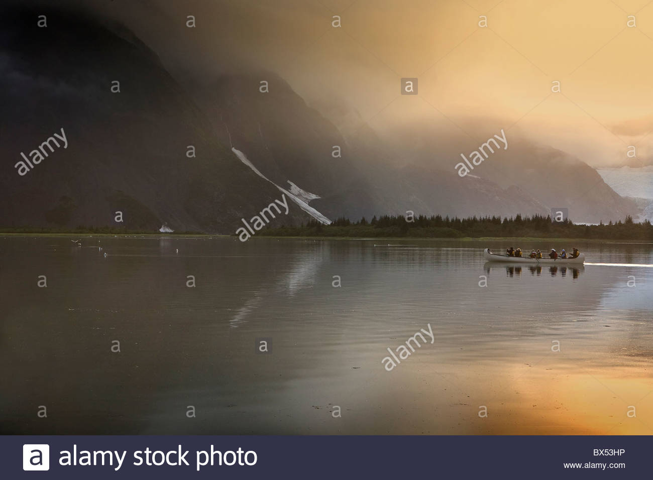 A canoe full of visitors makes its way across Pedersen Lagoon amidst some dramatic morning light. - Stock Image