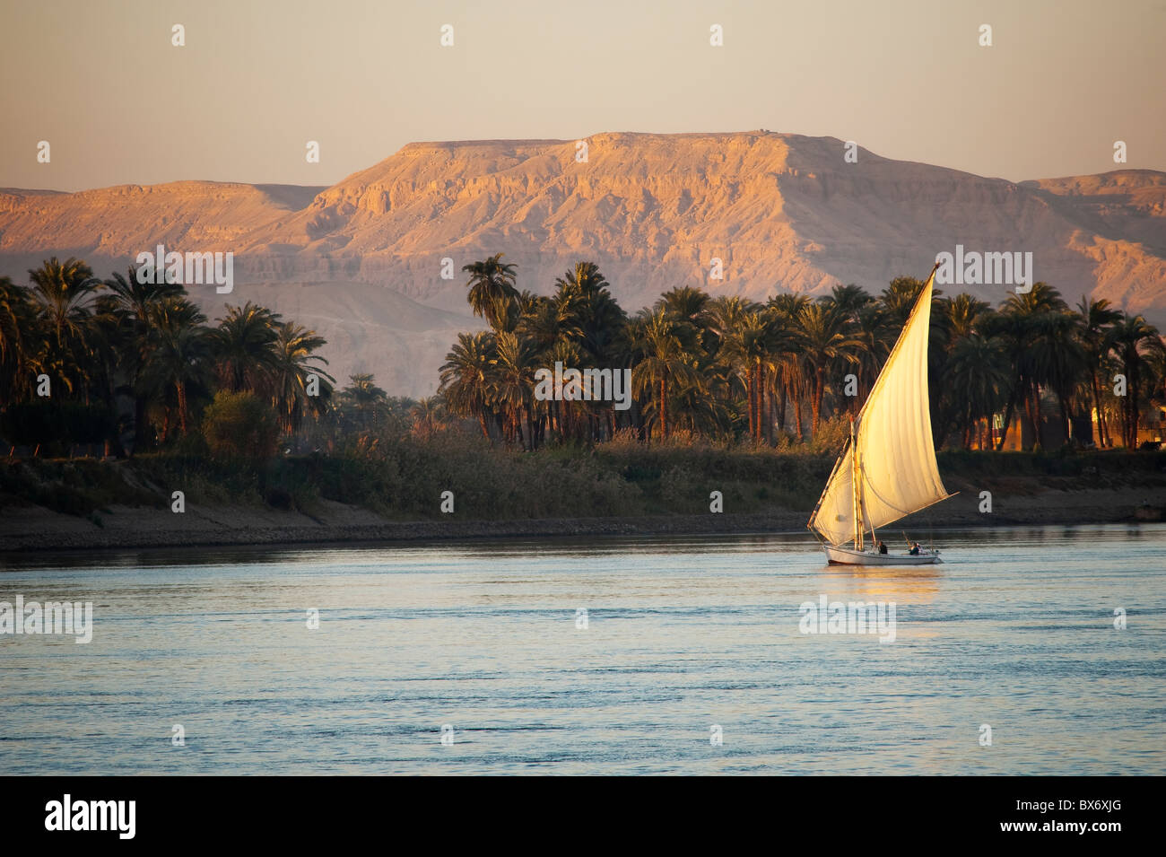 A stunning and beautiful image of a traditional Egyptian sail boat called a felucca on the Nile at sunset with mountains - Stock Image