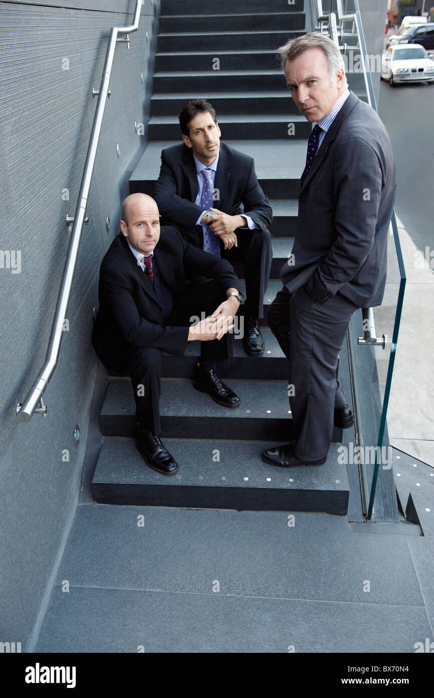 Business colleagues hanging out in stairs - Stock Image