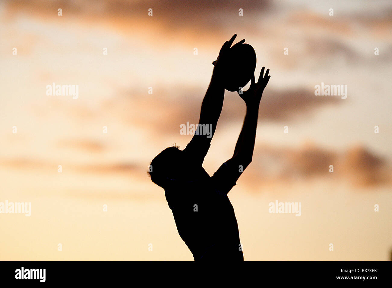 Rugby silhouette player with ball with Sun Set - Stock Image