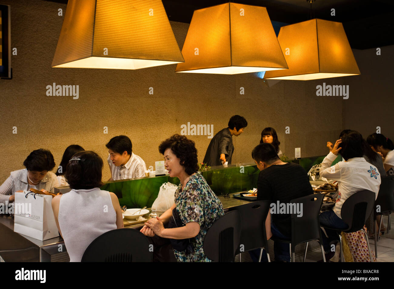 Wealthy Koreans eating lunch at a restaurant at Lotte Department Store - Stock Image