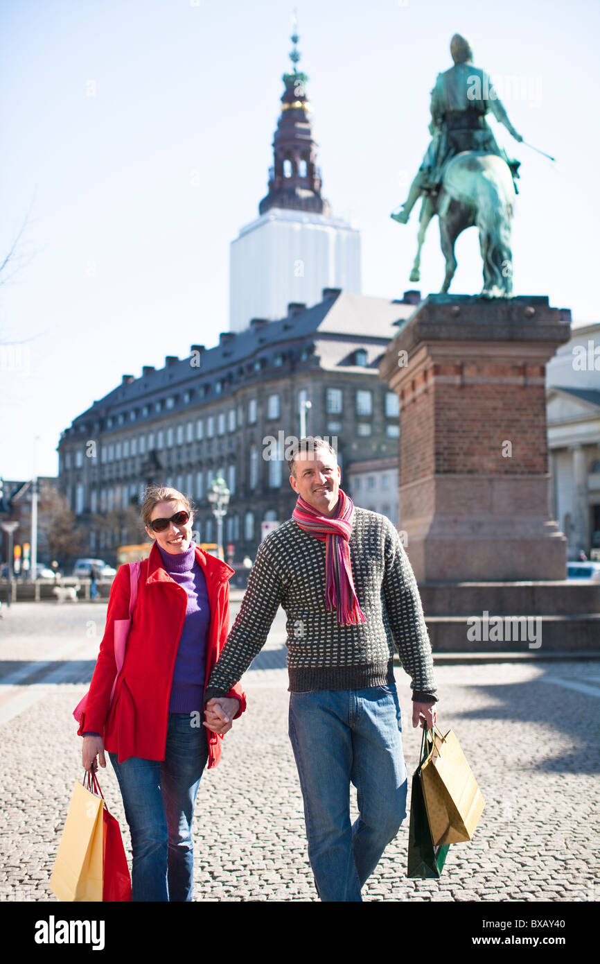 Couple with shopping bags, walking in city - Stock Image