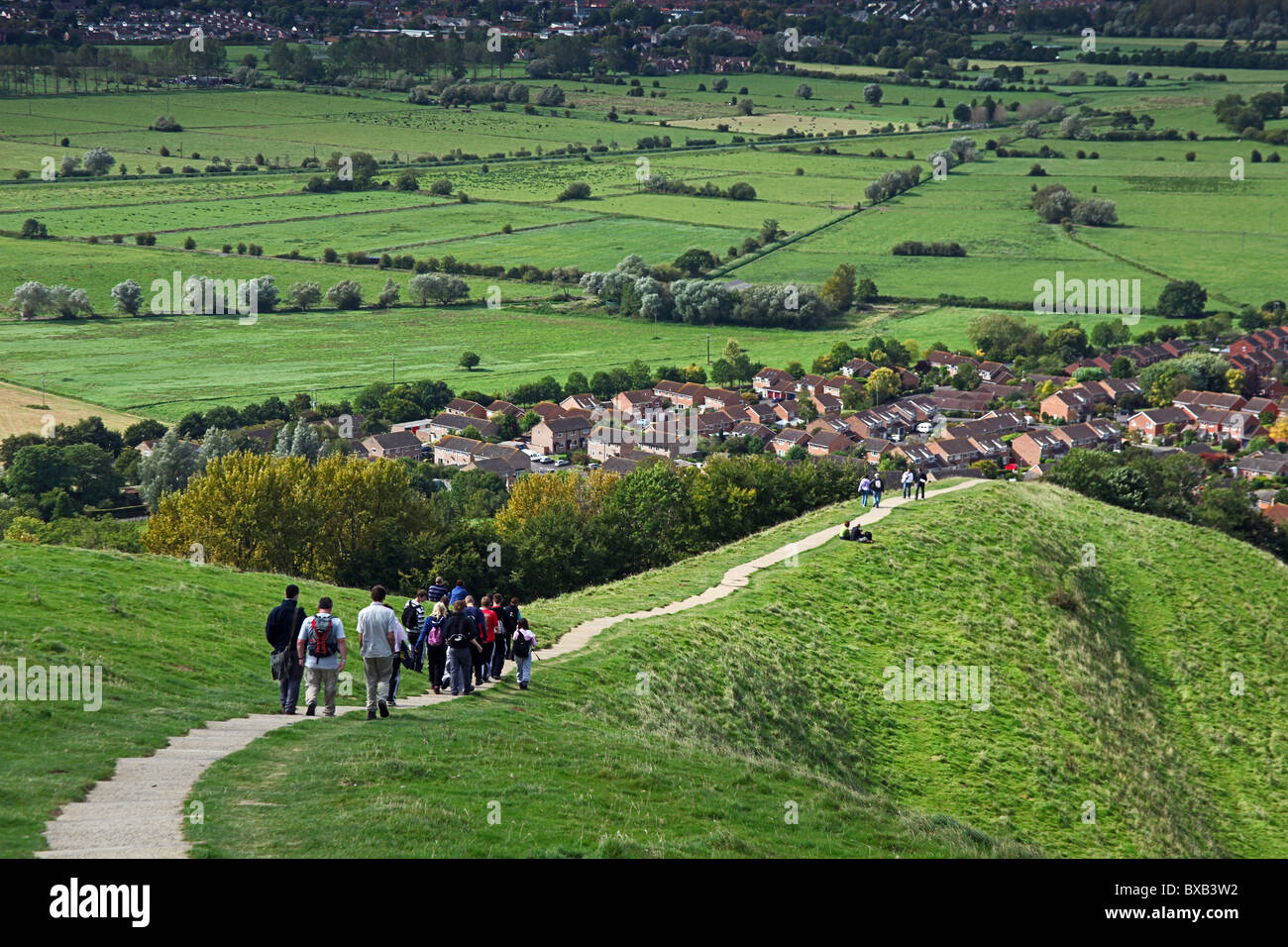 A group of walkers on the path leading from the summit of Glastonbury Tor which overlooks the Somerset Levels, England, - Stock Image