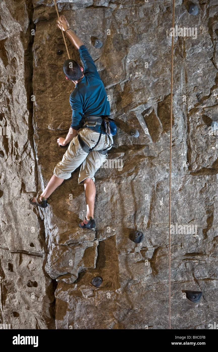 Rock Climber Climbing Indoor Rock Wall - Stock Image