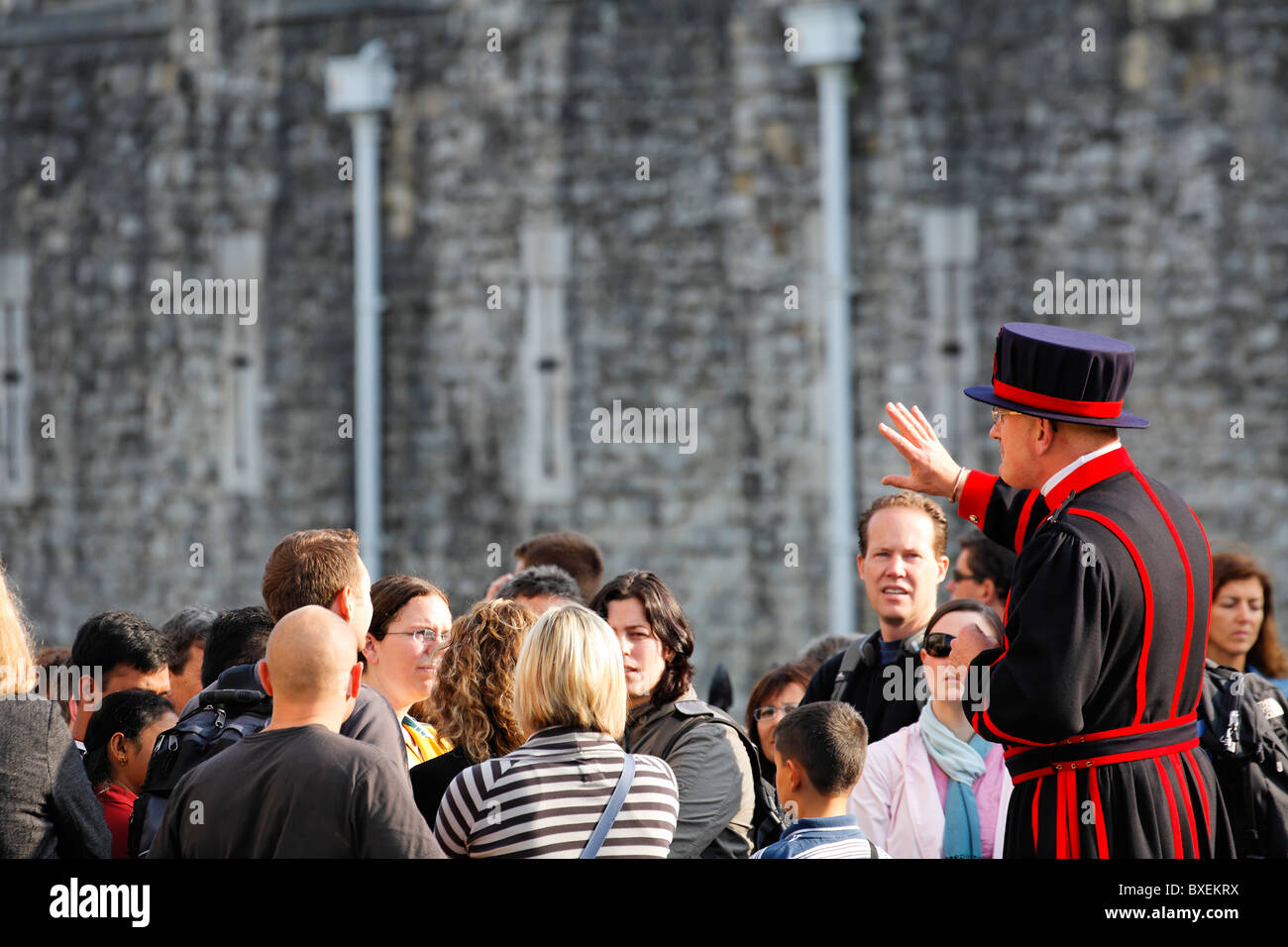 Beefeater with a tour group at the Tower of London, UK - Stock Image