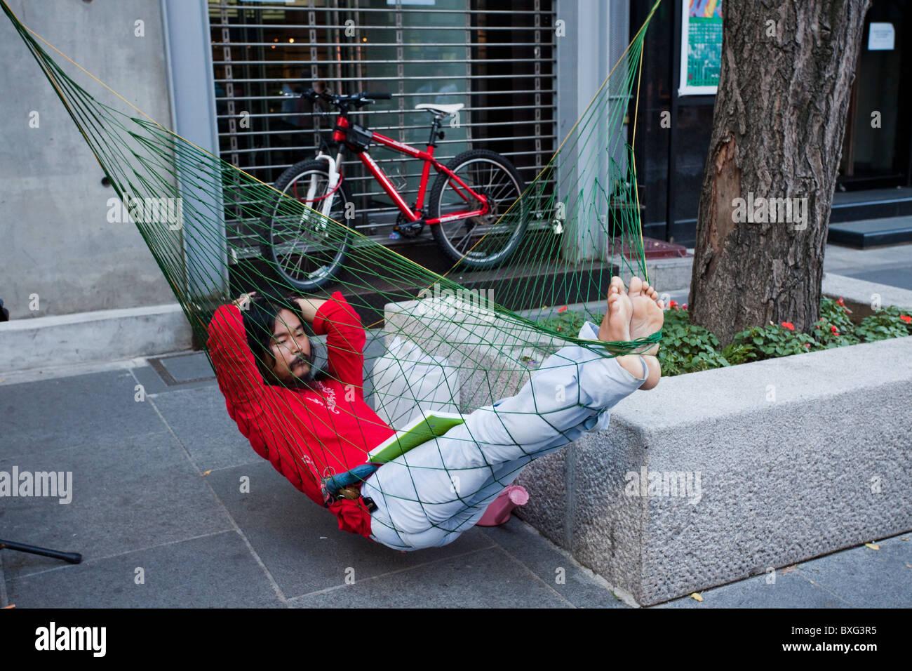 Korea man is reading in a hammock in Seoul's street, Seoul, South Korea - Stock Image