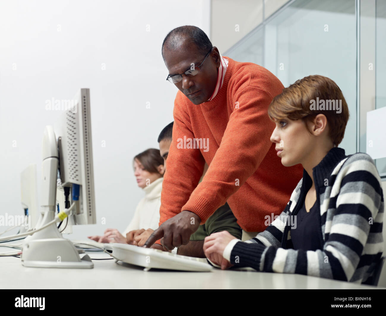 Computer class with indian male teacher helping female student. Horizontal shape, side view, waist up, copy space - Stock Image