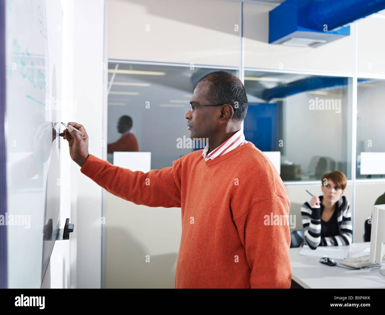 Computer class with indian male teacher writing on board and students in background. Horizontal shape, side view, - Stock Image