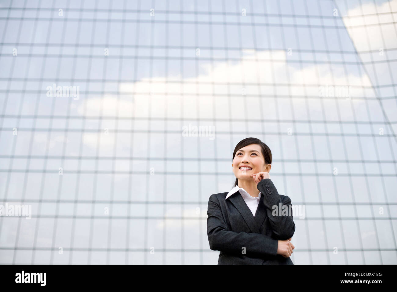 Businesswoman in front of a tall building - Stock Image
