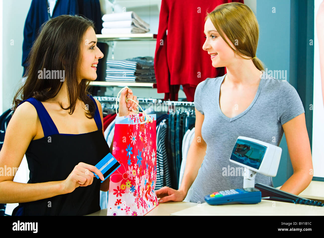 Portrait of a buyer and a shop assistant looking at each other with smiles by the pay desk in the clothing department - Stock Image