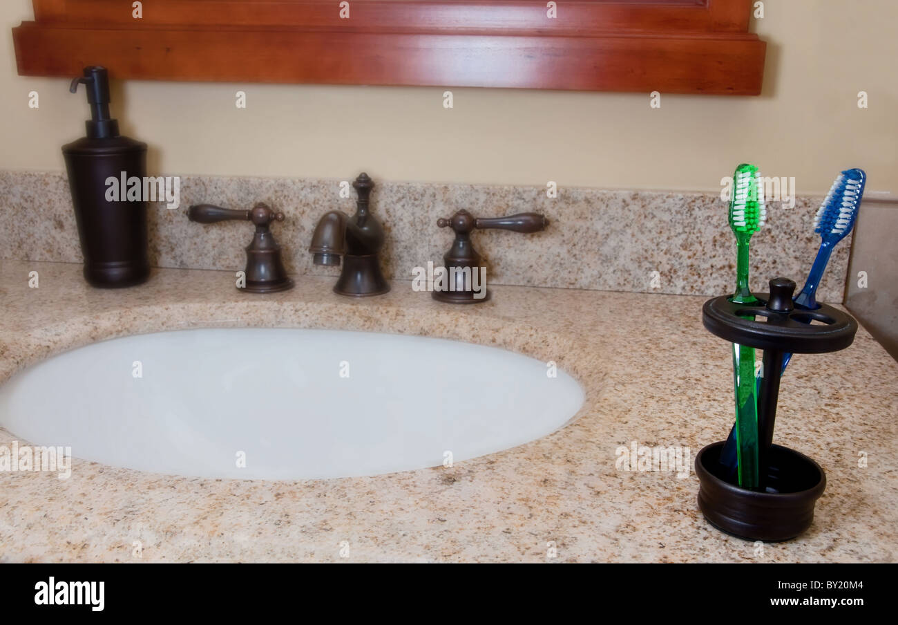 Bathroom Sink And Faucet With Toothbrushes And Soap Dispenser.