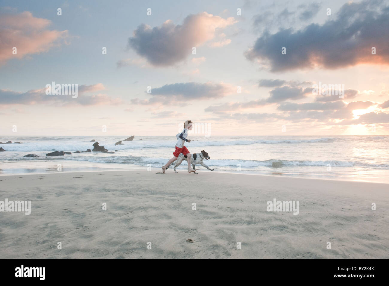 A young boy and dog run along a quiet beach in Mexico at sunset. - Stock Image