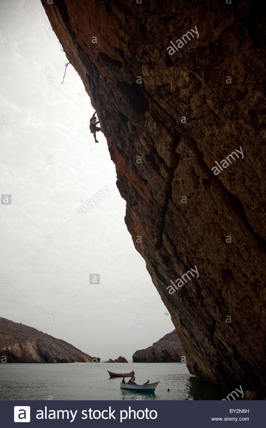 A young man freeclimbing a cliff 40' above the Caribbean - Stock Image