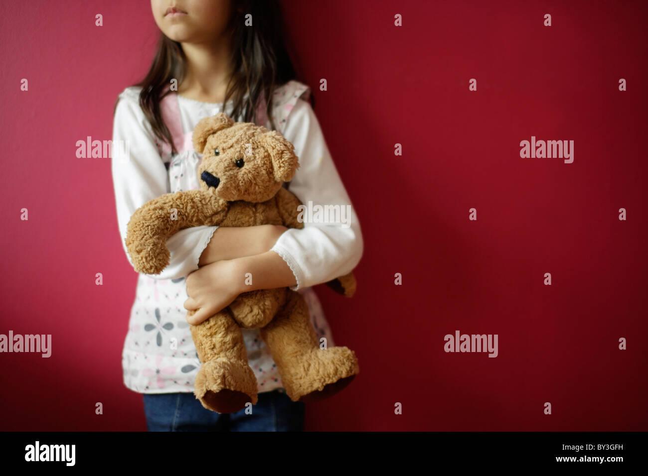 Girl holds teddy bear - Stock Image