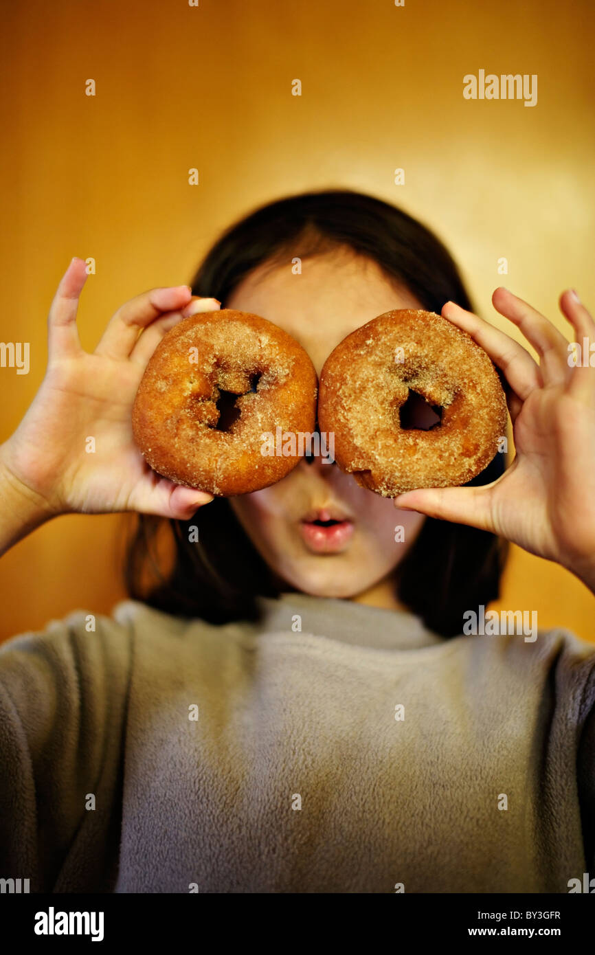Girl holding donuts over eyes. - Stock Image