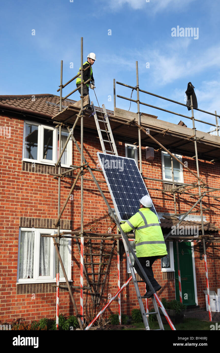 Installing photo voltaic solar panels onto the roof of a domestic house within Washington, North East England, UK Stock Photo