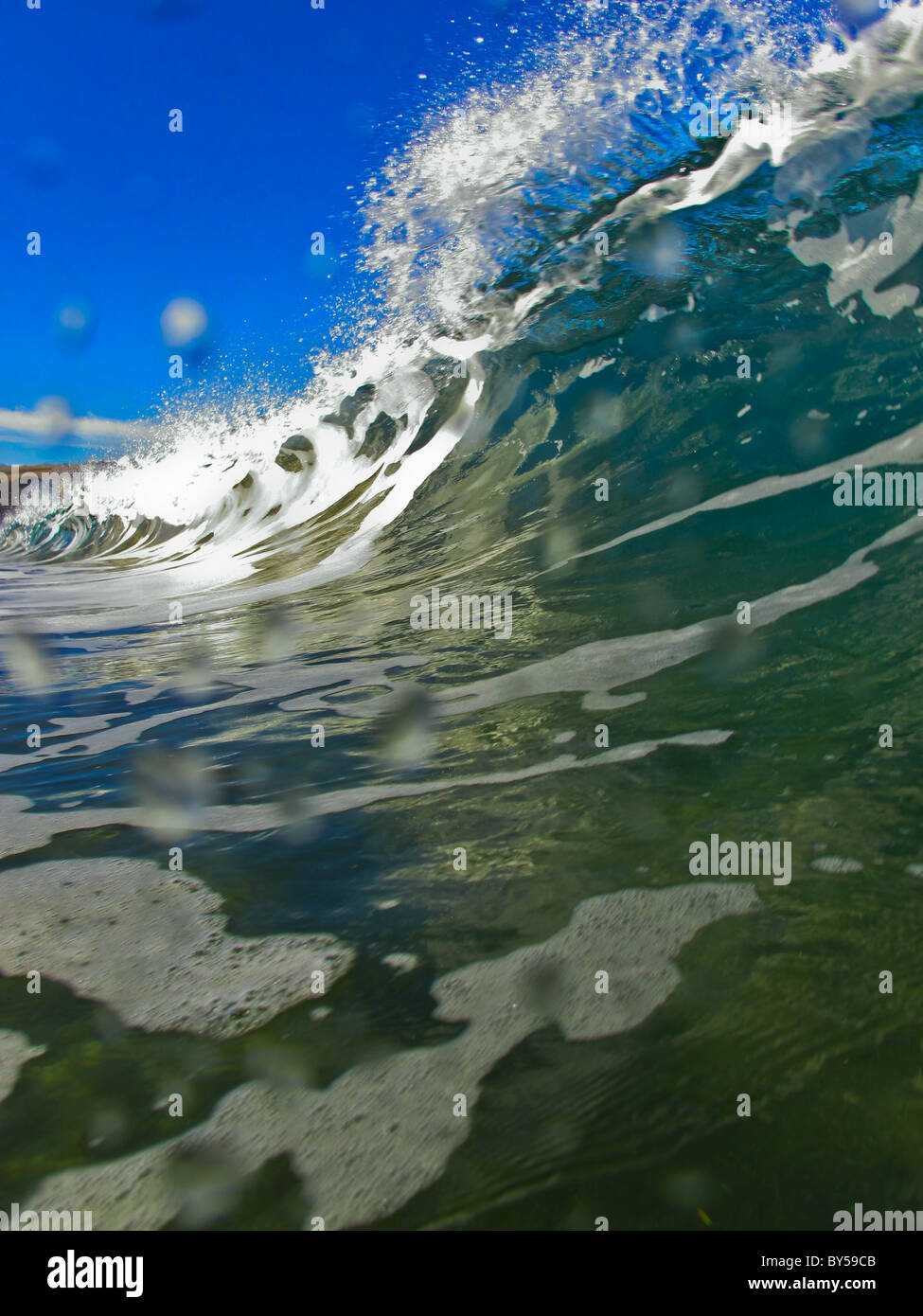 Breaking wave viewed from inside the water - Stock Image