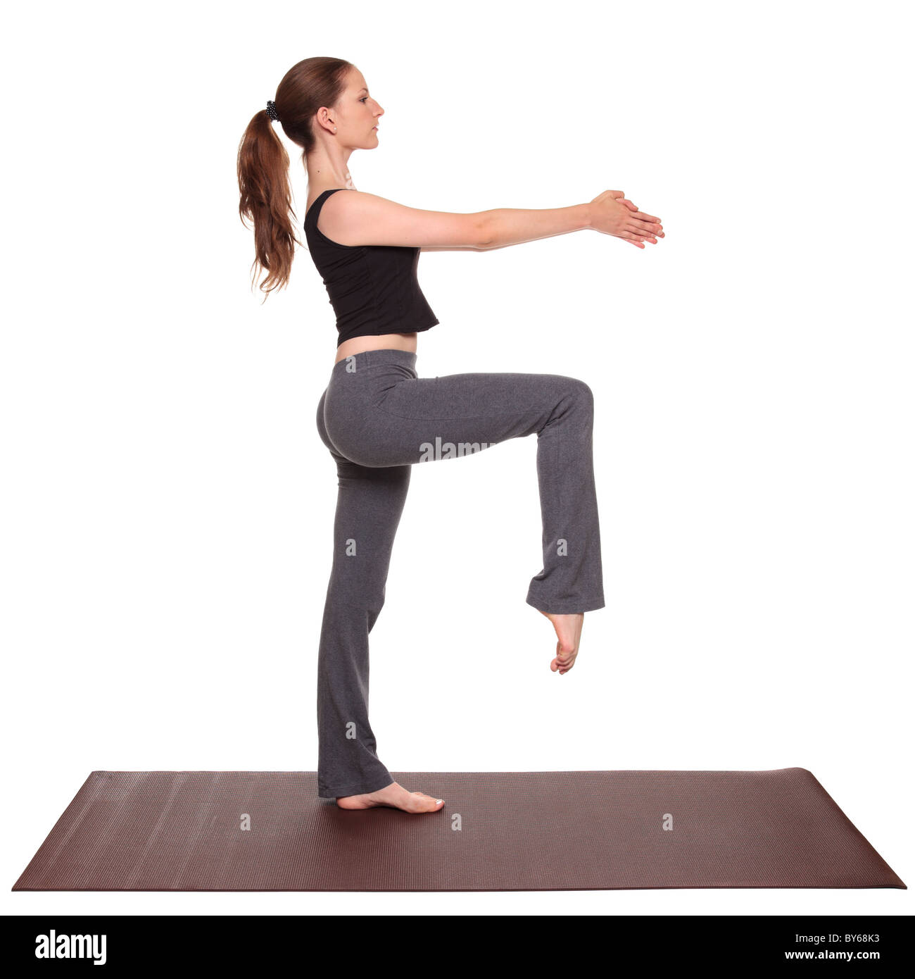 Isolated studio shot of a fit Caucasian woman holding the Stork Pose yoga position on an exercise mat. Stock Photo