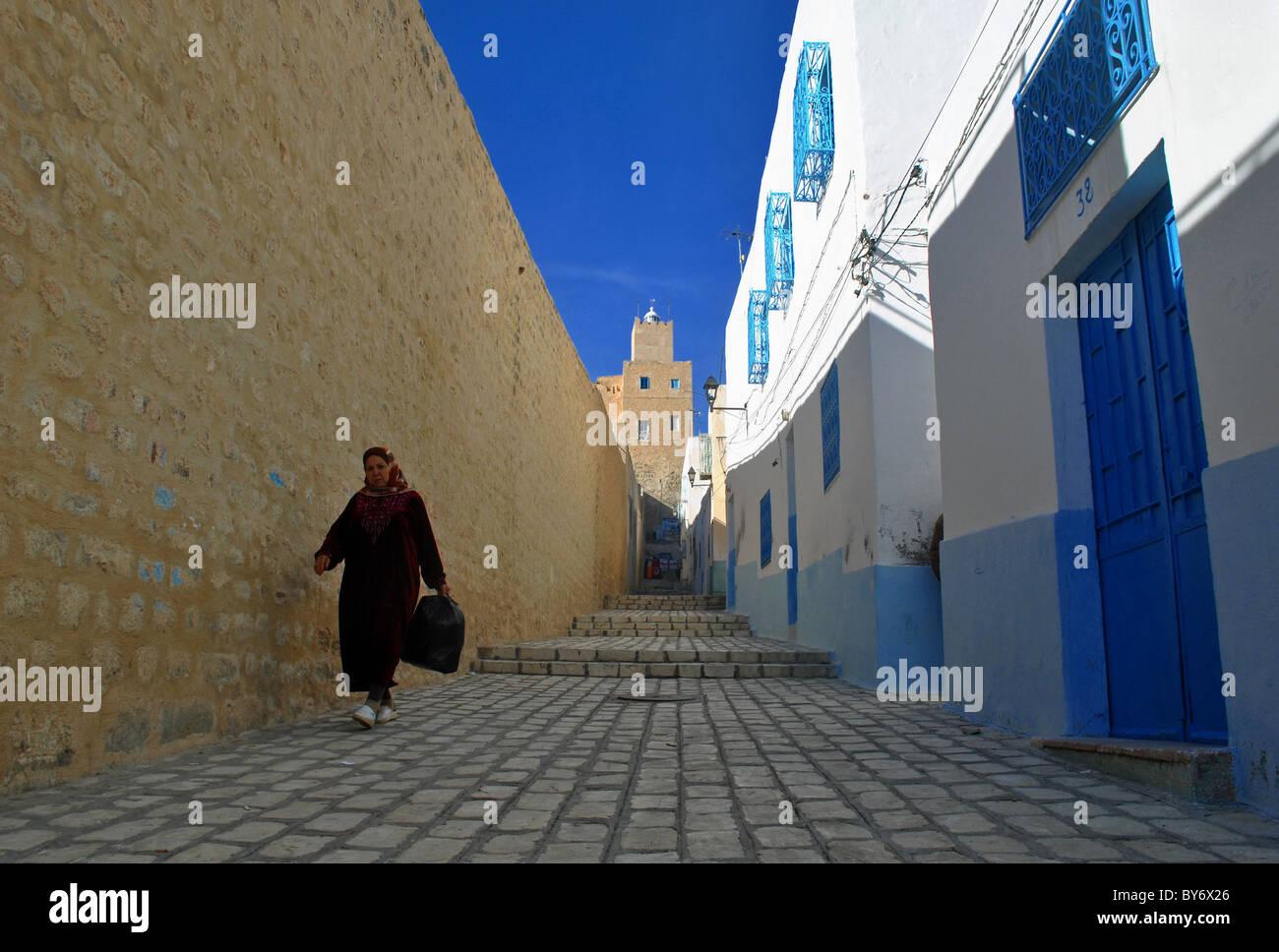 Woman walking down a street in Sousse medina, Tunisia - Stock Image