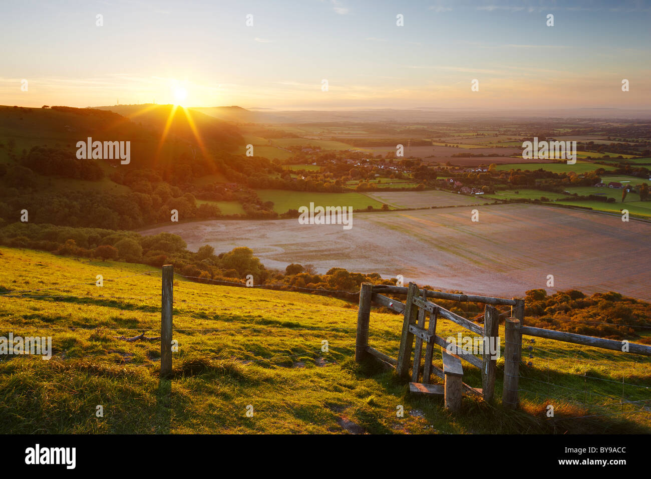 Stile with views across the West Sussex countryside. The evening sun making its descent behind the undulating Hillside. - Stock Image