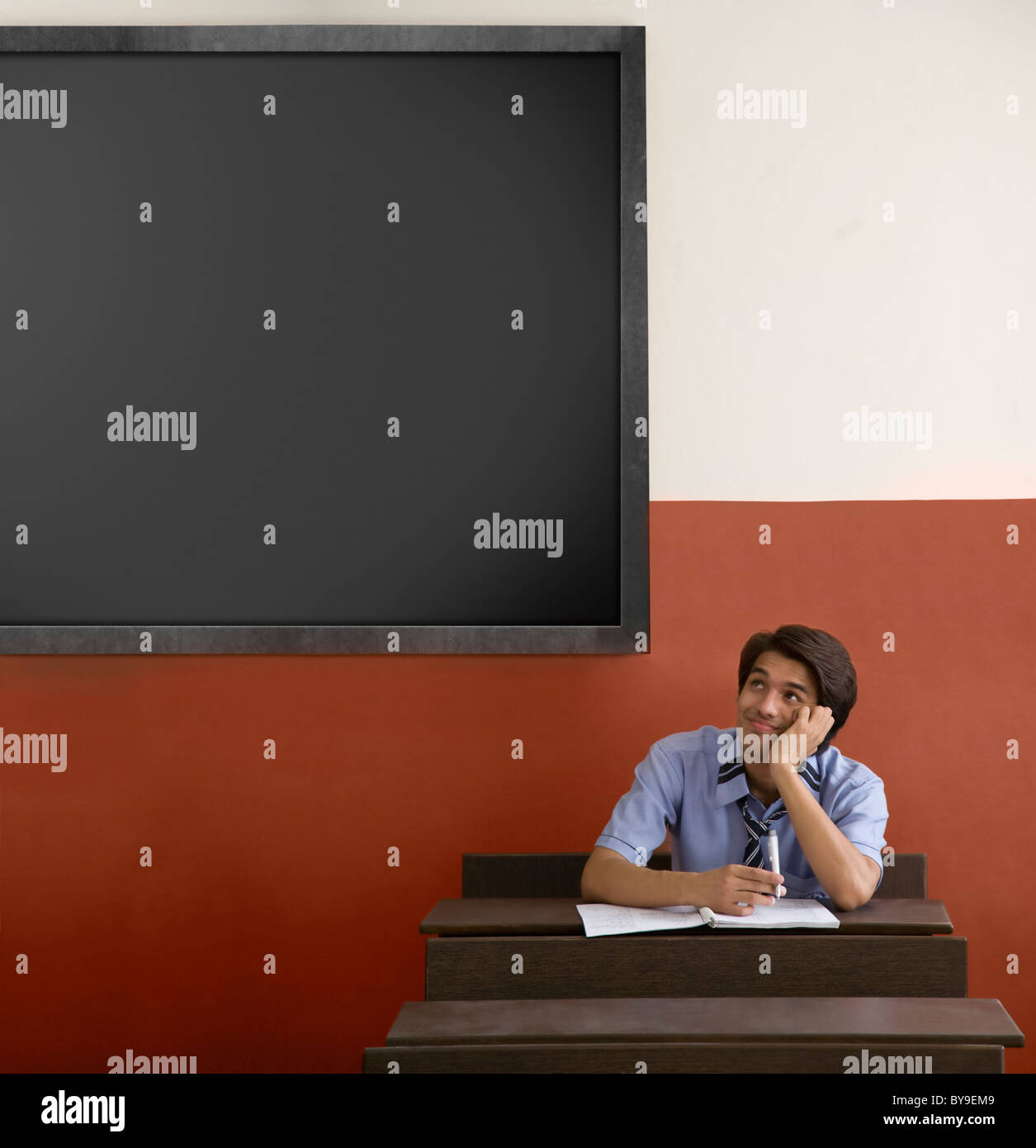 Boy daydreaming in a classroom Stock Photo
