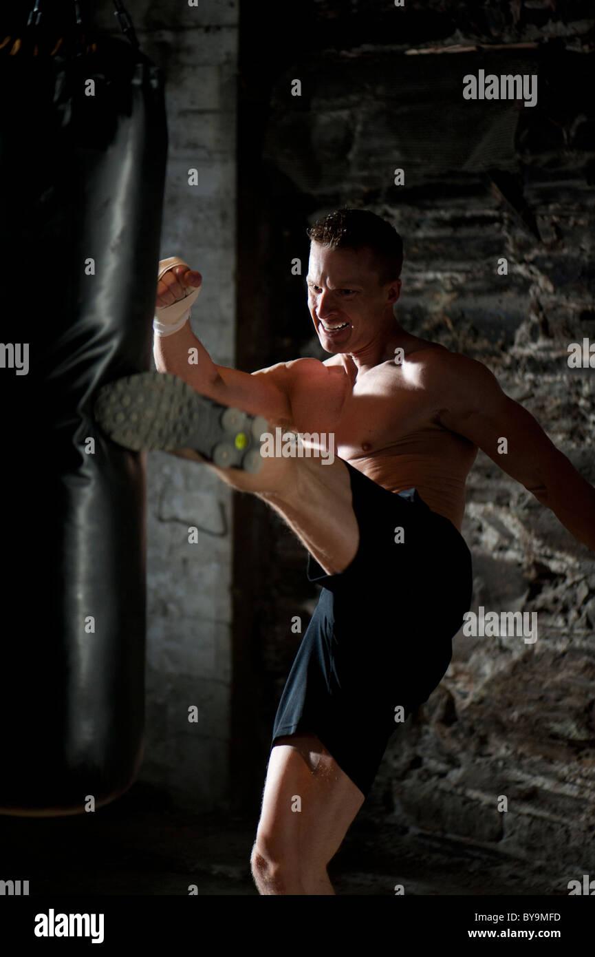 A man kick boxing at a gym. - Stock Image