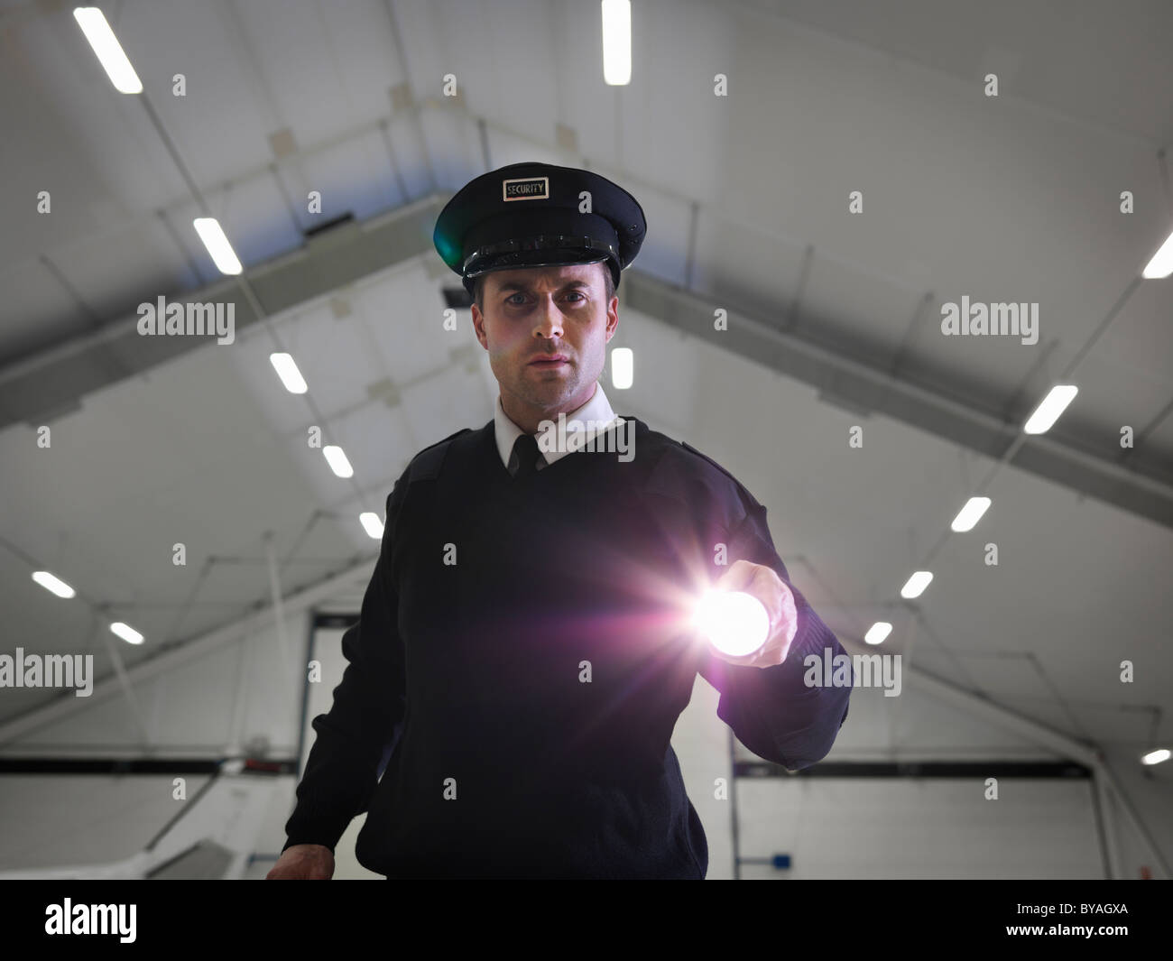 Security guard with torch in warehouse - Stock Image