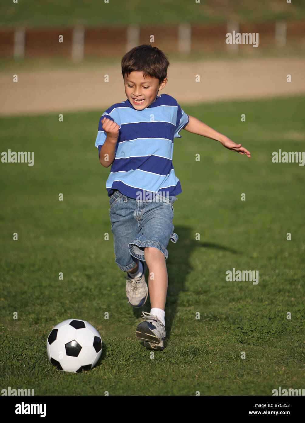 Authentic happy Latino boy playing with soccer ball in field wearing blue striped tee shirt. - Stock Image