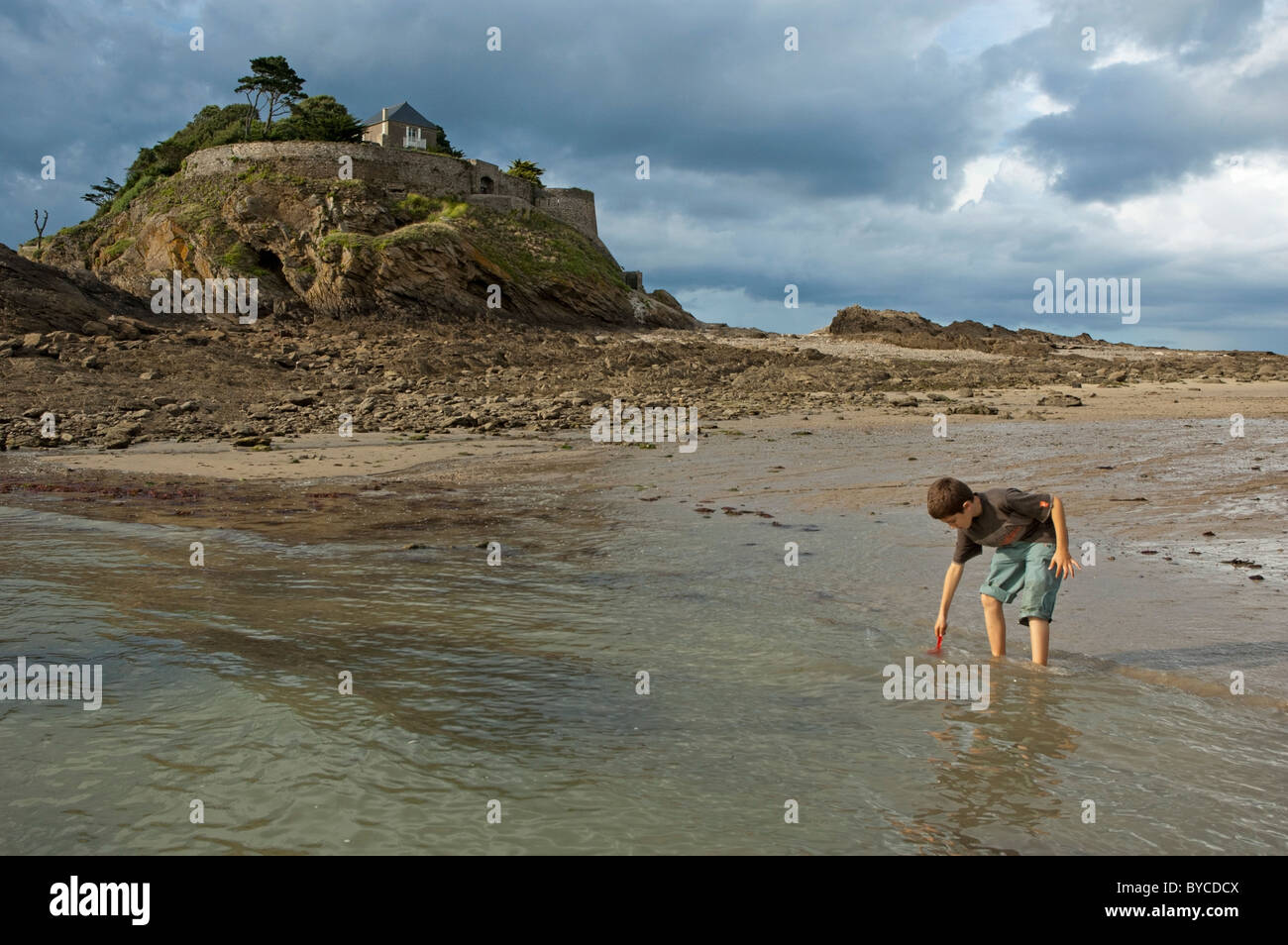 Boy playing in the sea at the water's edgenear the house on the rock called Anse du Guesclin in Brittany, France. - Stock Image