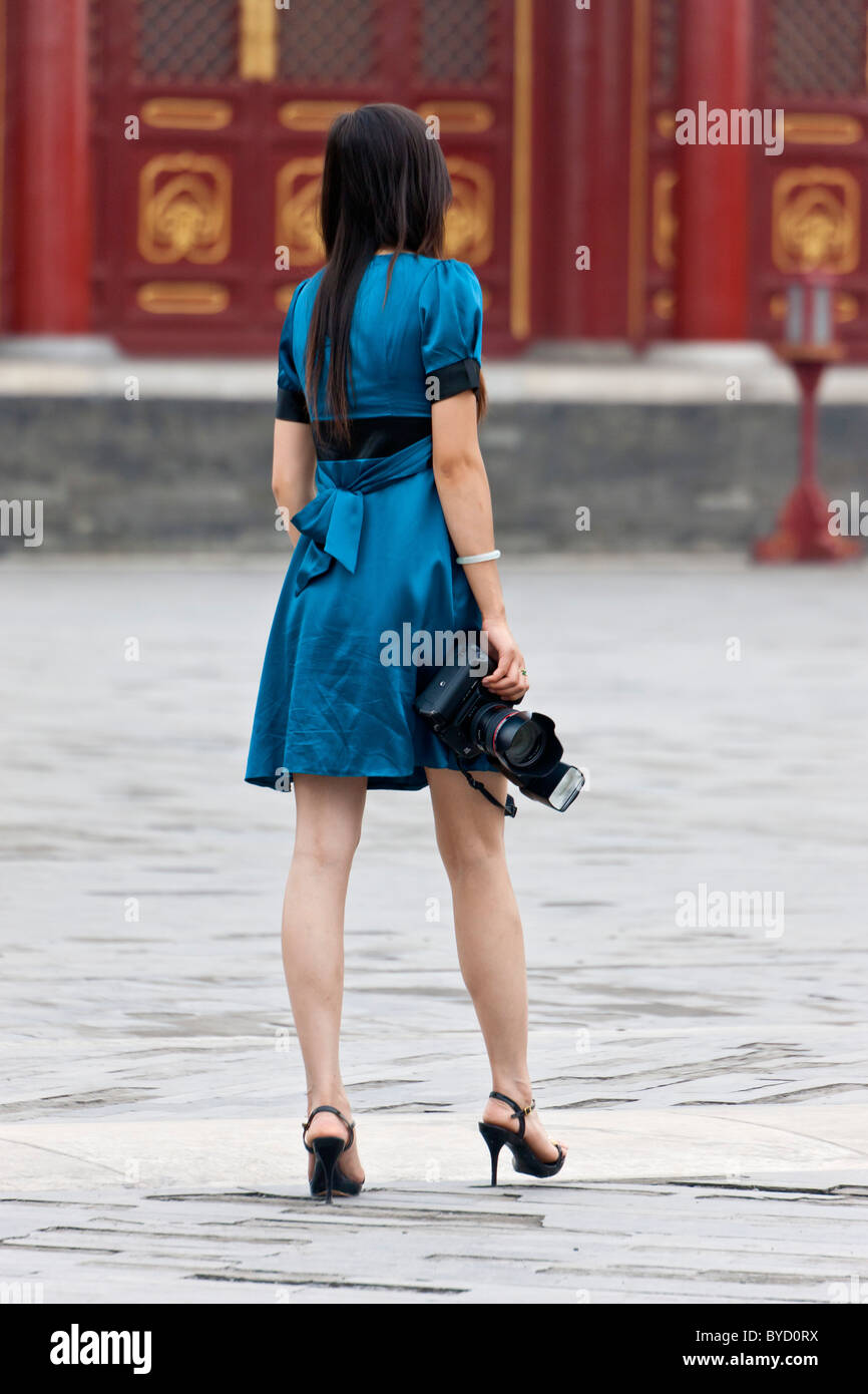 Elegant Chinese young woman in blue dress holding Canon DSLR camera with flash gun in the Temple of Heaven in Beijing. - Stock Image