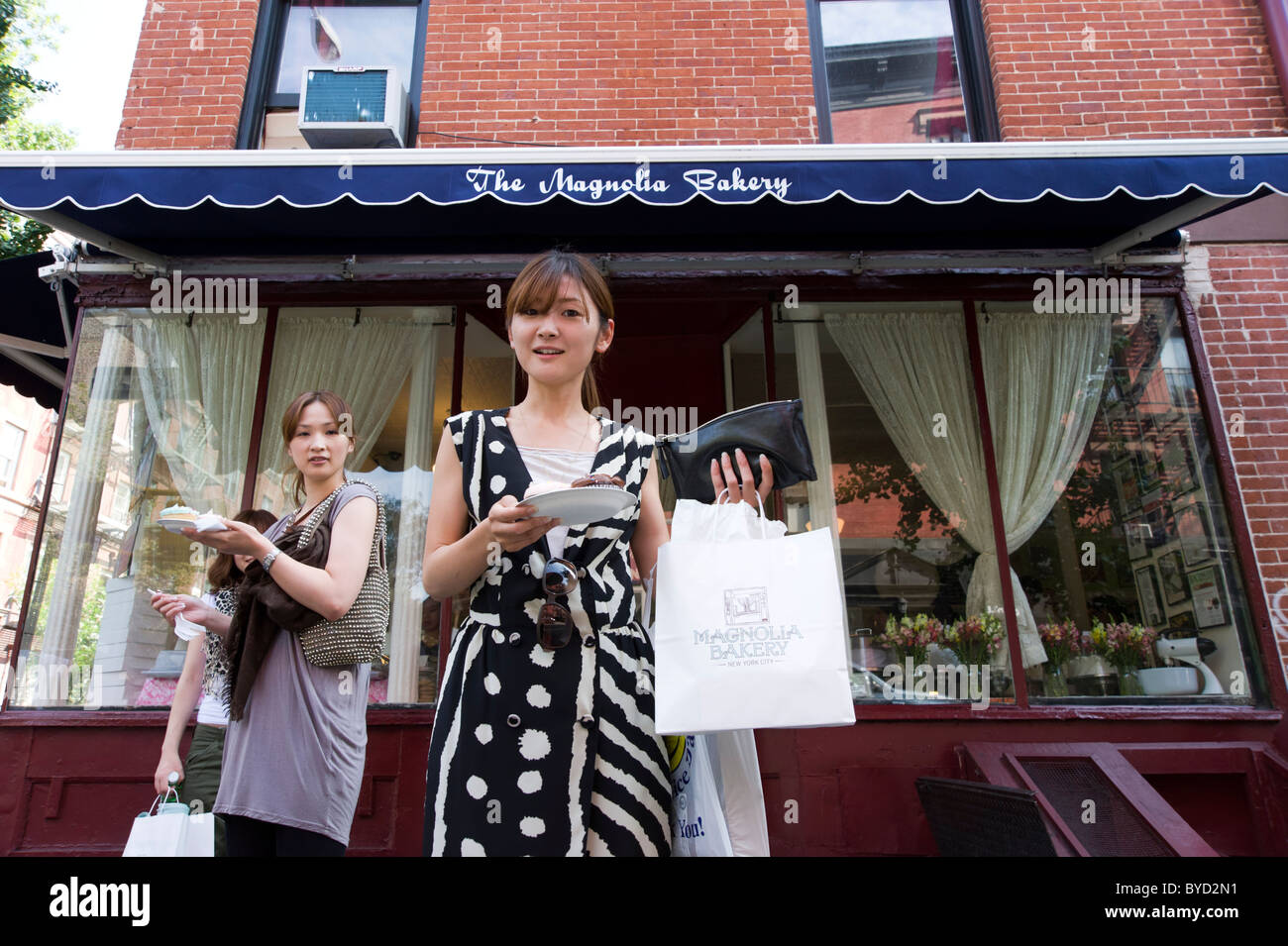 Japanese tourists buying cupcakes at The Magnolia Bakery which featured in Sex and the City, Bleecker Street, New Stock Photo