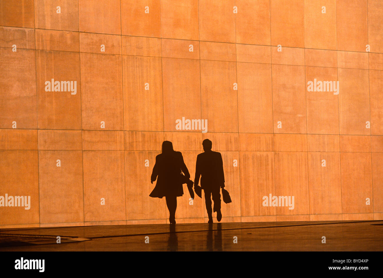 two-office-workers-silhouetted-against-t