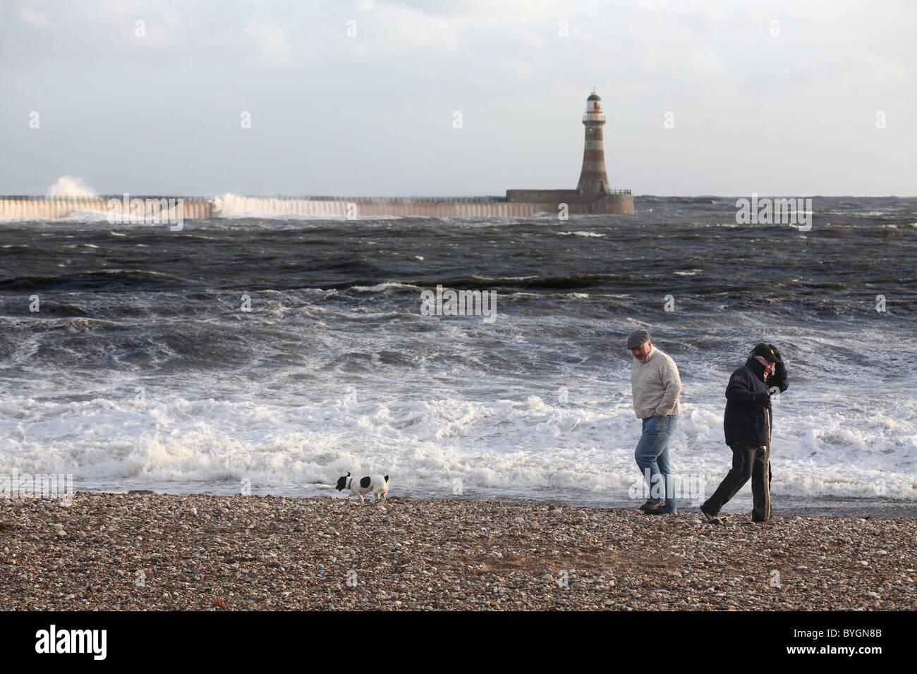 men-walking-on-roker-beach-with-a-dog-in